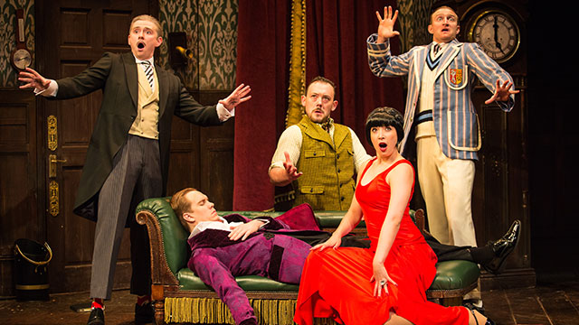 Cast members seated and standing around a man lying on a sofa with shocked expressions on their faces
