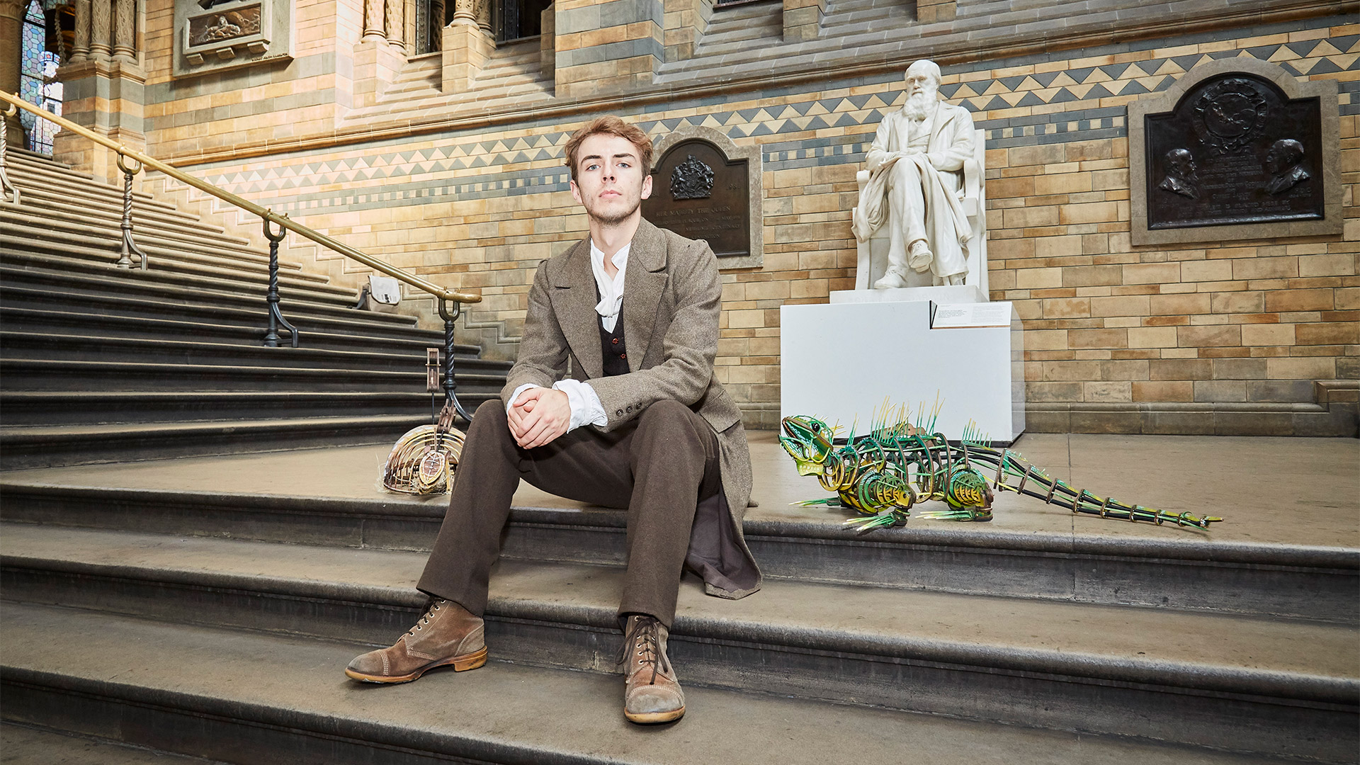 Bradley Foster poses on the steps of the Natural History Museum beside a small dinosaur model.