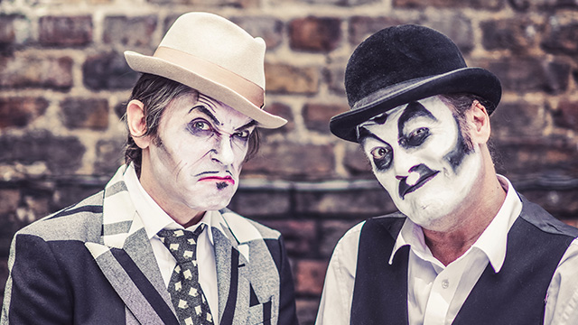 Two cast members of Tiger Lillies' Christmas Carol, wearing black and white face paint and hats.
