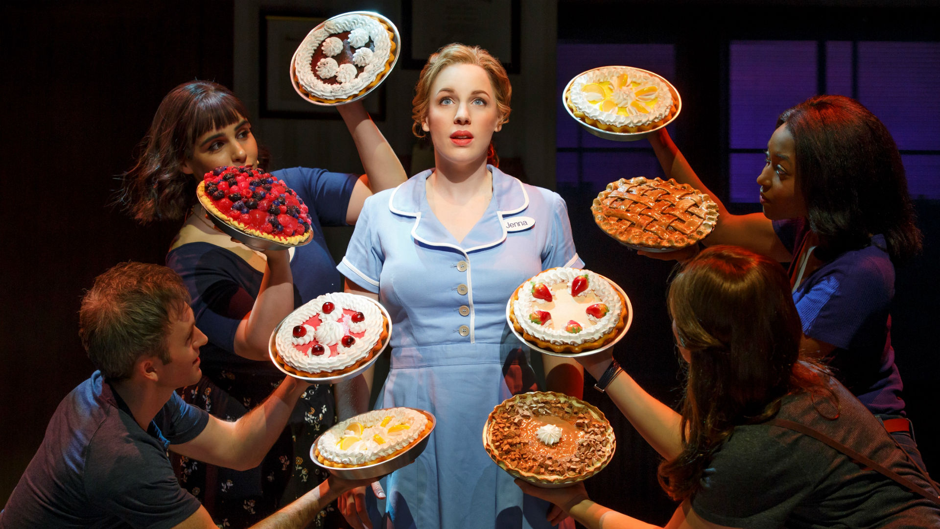 A waitress is standing surrounded by 4 people looking at her and holding pies and cakes close to her
