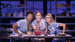 Three waitresses sit at a kitchen table. One holds a handful of flour in the upturned palm of her hand which is stretched out in front of her, all three are blowing on the flour so that it swirls upwards and away from them.