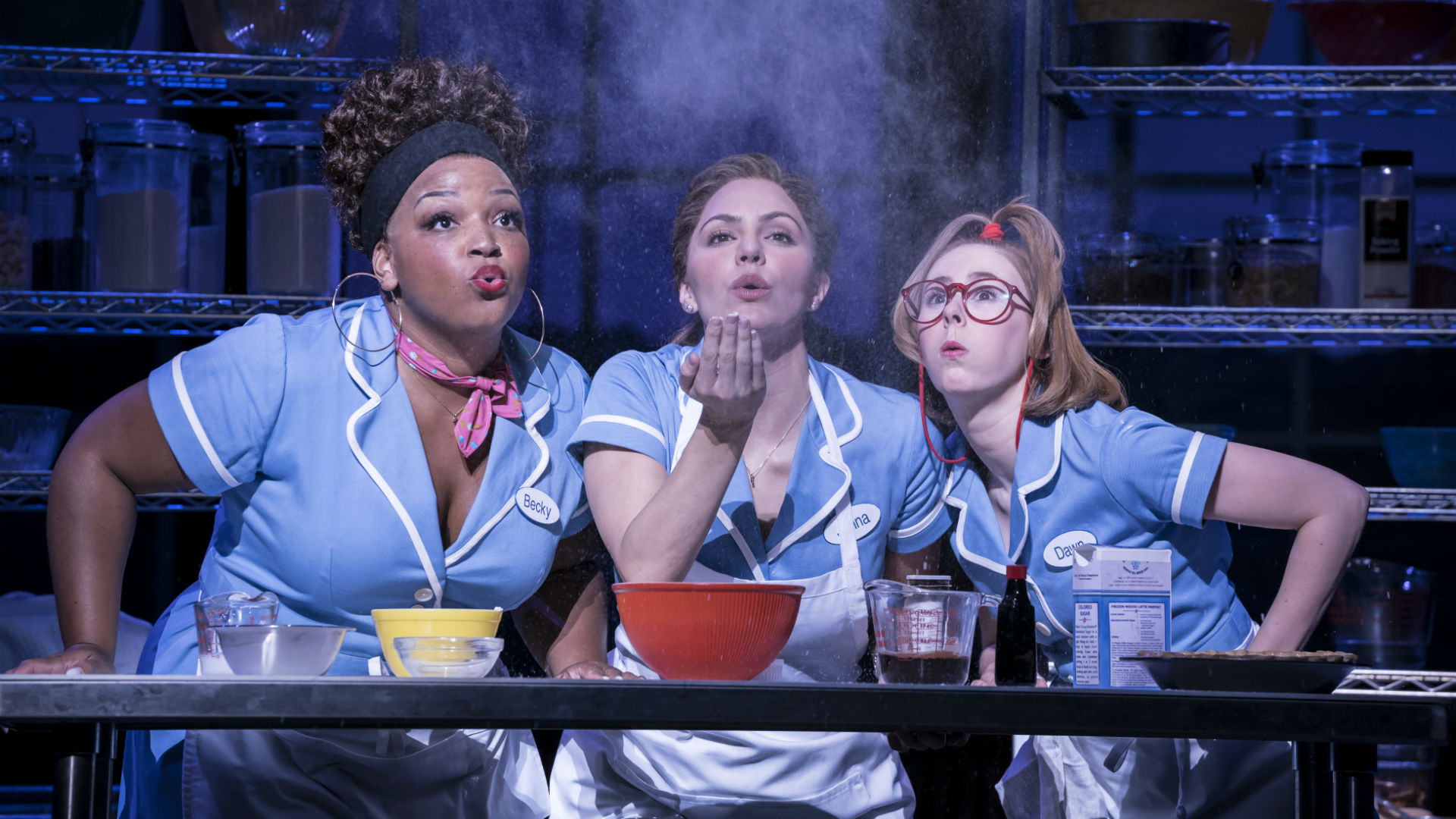 Three waitresses sit side by side at a kitchen table. One holds out a handful of flour in front of her and all three blow lightly to make the flour rise up into the air.