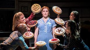 A waitress stands, facing forwards and surrounded by four people holding eight different pies.