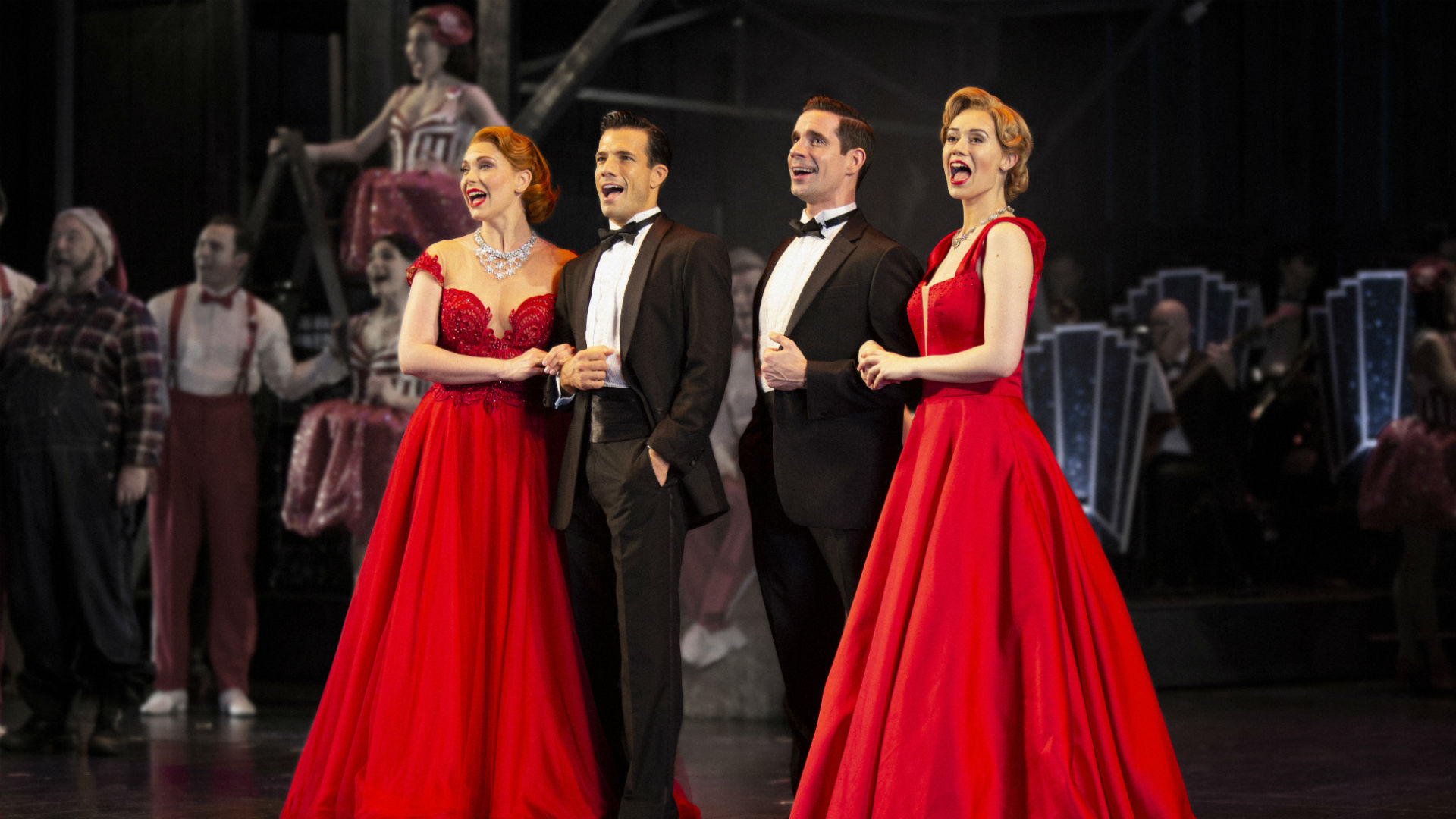 Two men in tuxedos stand arm-in-arm with two girls in red ballgowns. All four are singing.