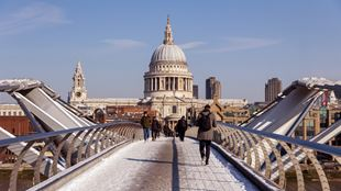 People walking across the London Millennium Bridge in the snow against the backdrop of St Paul's Cathedral.