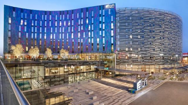 A view of the glass exterior of Aloft London ExCeL at dusk, with lights on in the rooms.