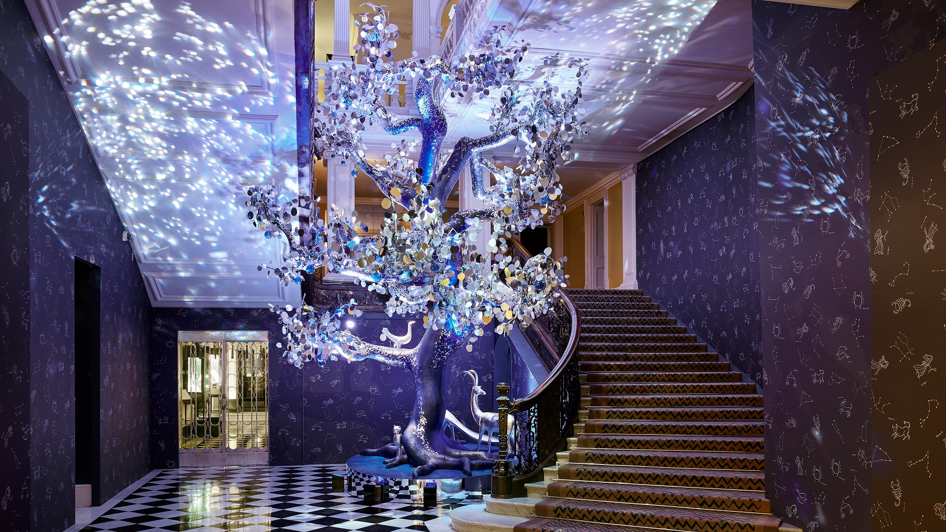 Claridge's Christmas tree shines with silver and glass decorations in a hall with black and white floor tiles.