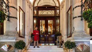 A smiling doorman dressed in an elegant red uniform is standing by the grand entrance of the Mandarin Oriental Hyde Park in Knightsbridge.