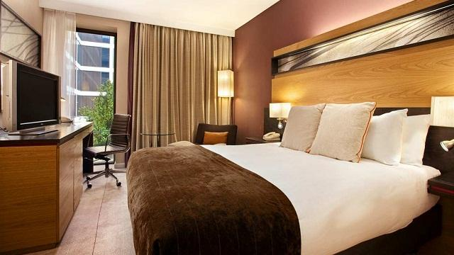 A room at Hilton London Gatwick, with a large bed featuring a brown throw, low-level lighting and a window.