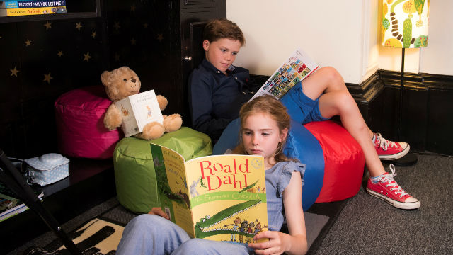 Children reading books from Le Meridien Piccadilly's kids' library. Image courtesy of Le Meridien Piccadilly.