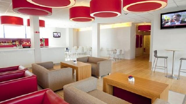A seating area within the Travelodge with red and beige seating, small wooden tables, a television and red light fittings.