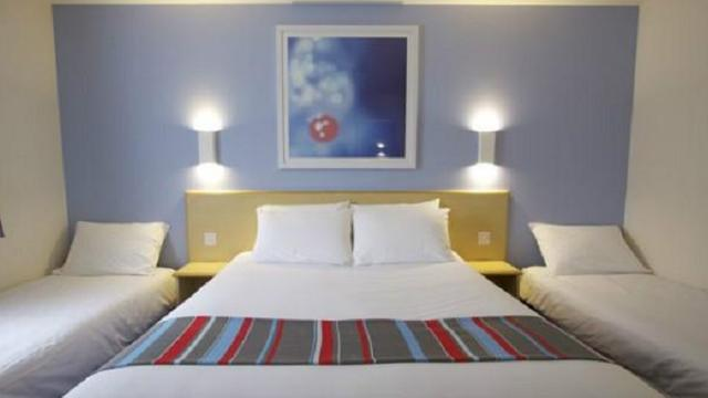 A room with a king-size bed, plus two single beds either side. A blue, grey and red striped throw is on the king-size bed and there is a painting above the headboard.