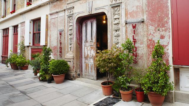 The main entrance of Wilton's Music Hall and red facade.