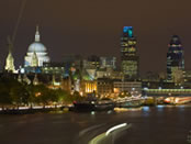 City of London waterfront and skyline, with the iconic domed roof of St. Pauls Cathedral illuminated at night