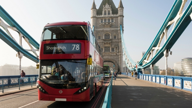 London red bus driving over Tower bridge