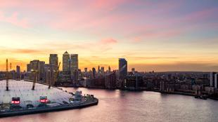 A beautiful sunset fills backdrops the London skyline and The O2.