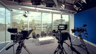 Three cameras point towards a table and chairs in a studio, with Tower Bridge in the background.