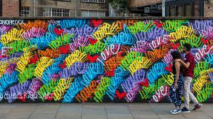 Two people walk past a wall filled with colourful street art