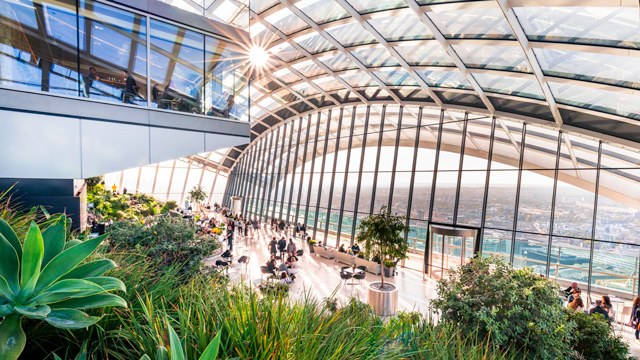 View across the atrium of the Sky Garden during the day with London visible in the background.