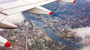 A view of London from an airplane featuring the plane's wing and clouds, with Tower Bridge, the river Thames and buildings across the city.