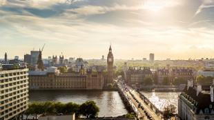 London's skyline, Big Ben and Westminster Bridge at dusk with the sun sparkling on the river Thames.