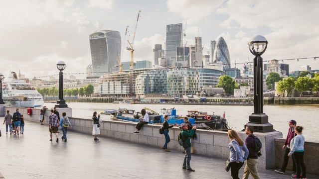 People walk along the sidewalk of the river Thames