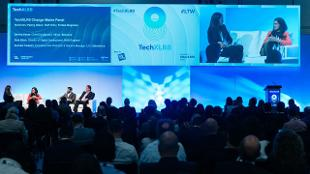 An audience watches a panel discussion on stage as part of London Tech Week.
