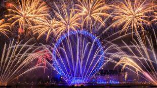 Golden fireworks explode about the blue London Eye