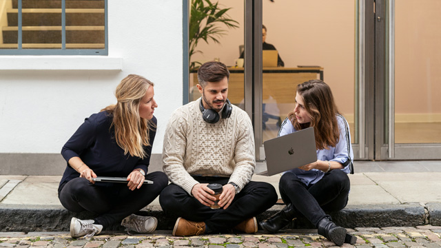 Three people sitting outside of London office discussing work on laptop.