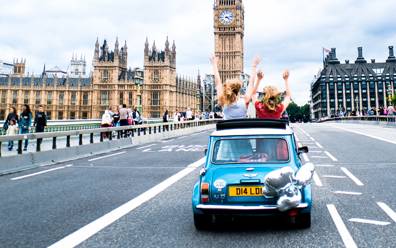 Two people wave their hands in the air as they are driven over Westminster Bridge towards Big Ben in a Mini Cooper