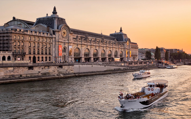 Two boats cruise along the Seine at sunset.