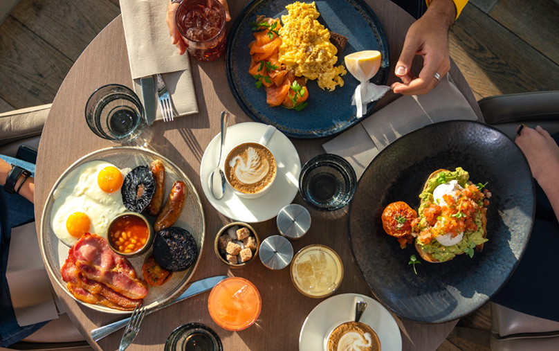 Overview of a table filled with delicious breakfast treats, including a full English breakfast.