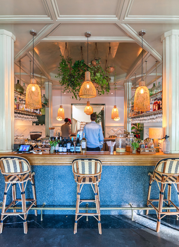 A trendy Parisian bar stocked with bottles of wine, hanging plants and contemporary lights.