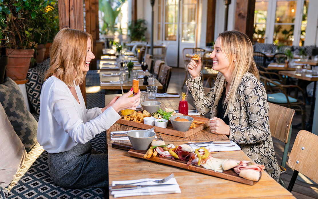 Two girls tuck into a plate of food in a contemporary restaurant.