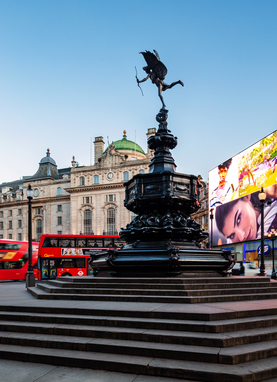 An iconic red London bus passes the Statue of Eros in Piccadilly Circus