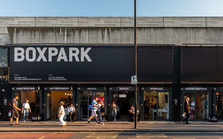 People wander past the shipping container shops of Boxpark.
