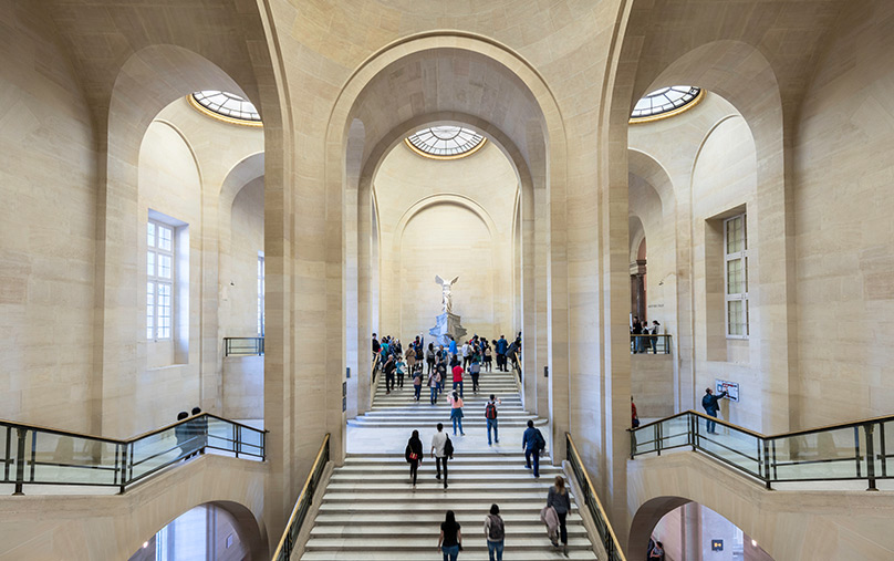 Visitors explore the inside of the marble-clad inside of the Louvre.