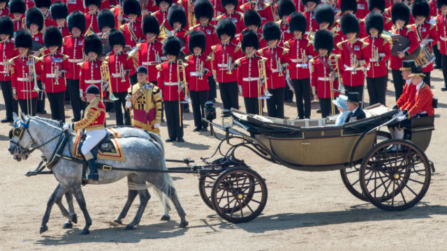 Horses pulling a vehicle in which the Queen is sitting, with guards wearing red uniforms in the background.